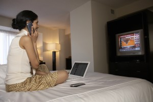 Woman on hotel bed with laptop and phone watching financial news