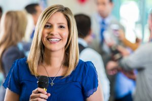 Blond smiling female news reporter stands in a blue shirt in front of a man addresing the media. She holds a microphone in hand.